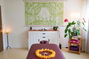 Praxisraum mit Blumenkette auf der Massageliege